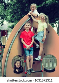 portrait of happy children playing together on climbing toy on urban playground