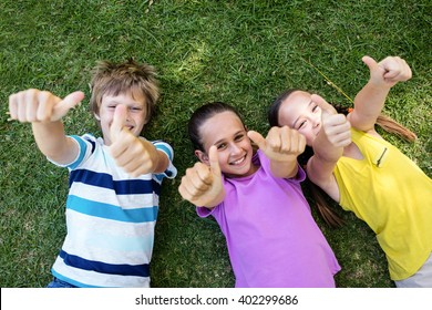 Portrait of happy children showing thumbs up while lying on the grass in park
