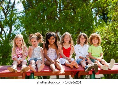 Portrait of happy children sitting together wooden structure in park.