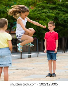 portrait of happy children skipping together with chinese jumping rope urban playground focus on boy