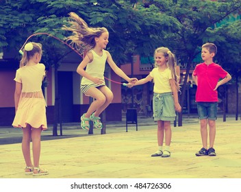 portrait of happy children skipping together with jumping rope on urban playground
