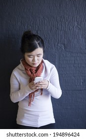Portrait of a happy Chinese woman leaning against a using her phone. Lifestyle image.