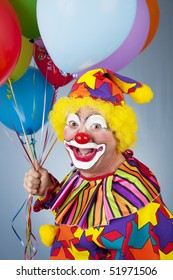Portrait of happy clown holding a bunch of helium balloons.
