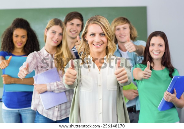 Portrait of happy college students gesturing thumbs up