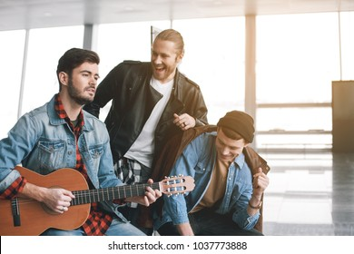 Portrait of happy comrades singing song. Smiling young male playing guitar indoor. Amity concept