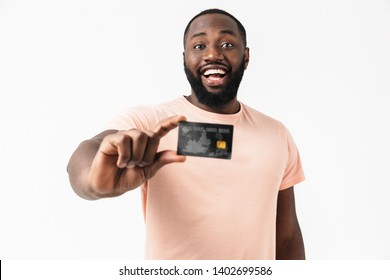 Portrait of a happy confident african man wearing shirt standing isolated, showing credit card