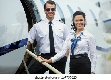 Portrait of happy confident airhostess and pilot standing on private jet's ladder