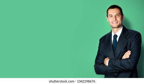 Portrait of happy confident businessman in black suit and blue tie, with crossed arms pose, empty copy space place for some text, advertising or slogan, standing against green color background