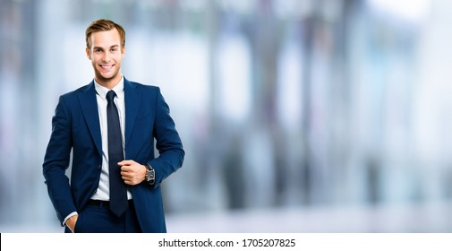 Portrait of happy confident businessman in blue suit and tie, over blurred office background. Business success concept. Smiling man indoors. Copy space for some text or slogan.
