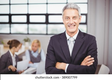 Portrait of happy confident businessman with colleagues in background