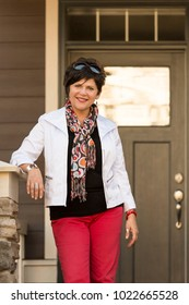 Portrait of a happy, confident, mature, middle-aged professional woman standing in front of a house. She could be the home owner or a real estate agent.
