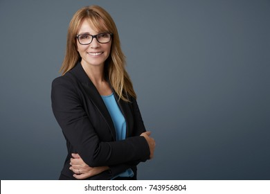 Portrait of a happy confident middle aged businesswoman standing with arms crossed at isolated background with copy space.
