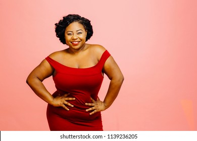 Portrait of a happy and confident plus size model in red dress, smiling