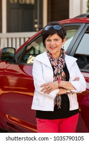 Portrait of a happy, confident, smiling, mature, middle-aged professional woman standing next to car near a house or home. She is wearing casual clothing.