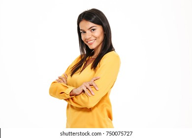 Portrait of a happy confident woman standing with arms folded and looking at camera isolated over white background