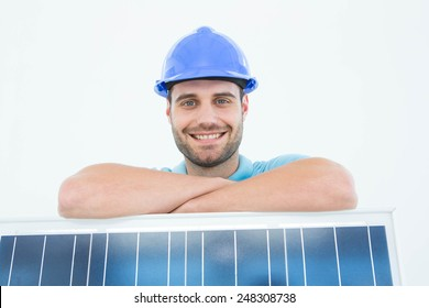 Portrait of happy construction worker leaning on solar panel against white background