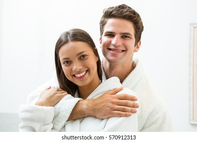 Portrait of happy couple in bathrobe embracing in the bathroom