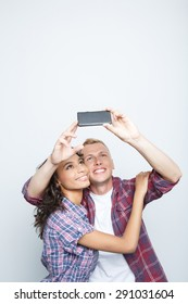 Portrait of a happy couple. Beautiful young mulatto girl and her blond boyfriend standing near hugging while the guy holding his smartphone above and making selfie, isolated on grey background