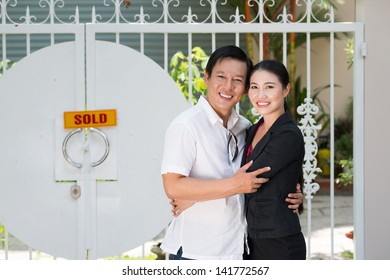 Portrait of a happy couple bonding in front of a their new bought house