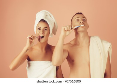 Portrait of happy couple brushing teeth in bathroom at home. Young couple cleaning teeth together at bathroom. Smiling woman face. Funny photo. Love concept. Bathroom concept.