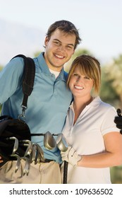 Portrait of a happy couple carrying golf bag on golf course
