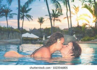 Portrait of happy couple, closeup body at swim at the swimming pool. Traveling at Bali. Open-air swimming pool