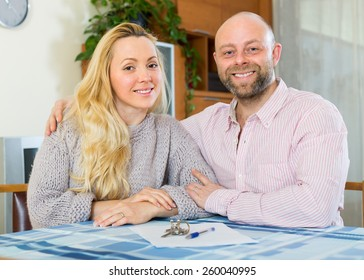 Portrait of happy couple with contract for buying apartment and keys