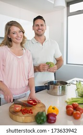 Portrait of happy couple cooking vegetables together at kitchen counter