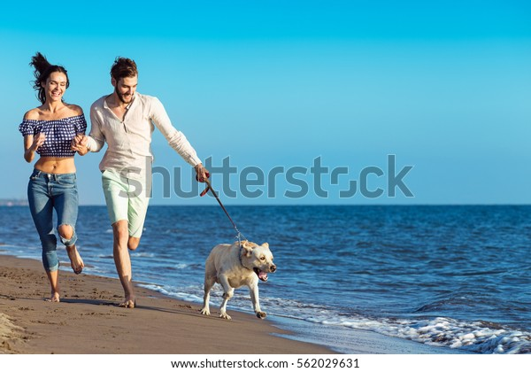 Portrait of a happy couple with dogs at the beach