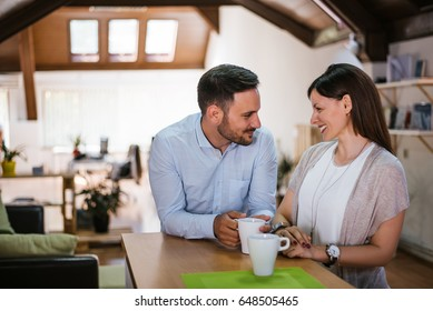 Portrait of happy couple drinking coffee by table at home
