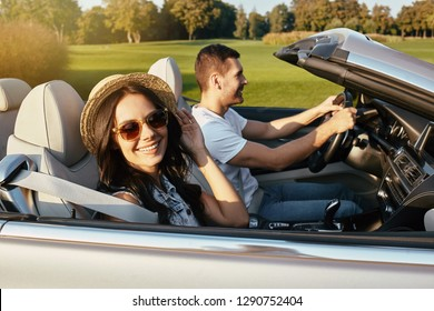 portrait of happy couple driving cabriolet in summer
