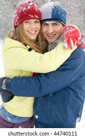 Portrait of happy couple embracing in winter forest during snowfall