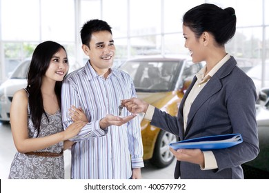 Portrait of happy couple get a car key from a car dealer in the showroom