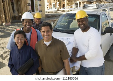 Portrait of happy couple with group of architects at construction site