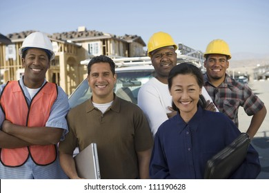Portrait of a happy couple with a group of architects at construction site