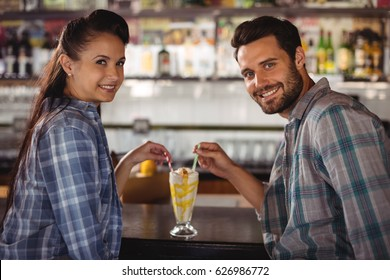 Portrait of happy couple having milkshake at counter in restaurant