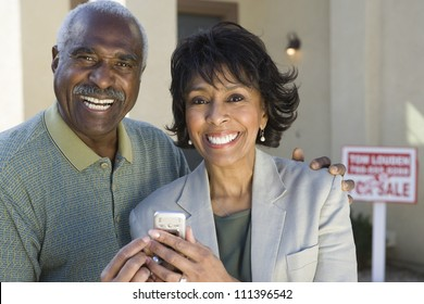 Portrait of happy couple holding cell phone in front on new house