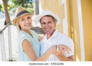 Portrait of happy couple holding hands in city