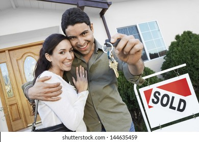 Portrait of a happy couple holding keys in front of their house by sold sign
