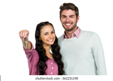Portrait of happy couple holding keys over white background