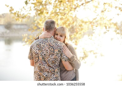Portrait of a happy couple hugging in the park with the woman face in foreground.  Portrait of a happiness woman hugging his boyfriend. Autumn