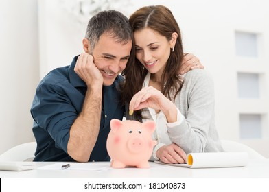 Portrait Of Happy Couple Inserting Coin In Piggybank