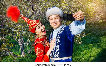 Portrait of Happy couple in Kazakh costumes doing selfie by cellphone in Spring Blooming apple garden of Almaty, Kazakhstan, Central Asia