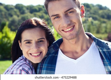 Portrait of happy couple laughing at camera and smiling outdoor closeup