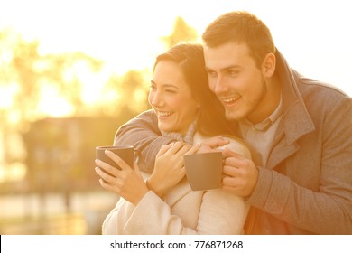 Portrait of a happy couple looking away holding coffee mugs in winter at sunset