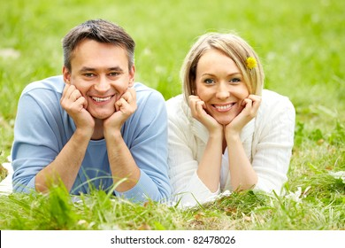 Portrait of happy couple looking at camera while lying on green grass