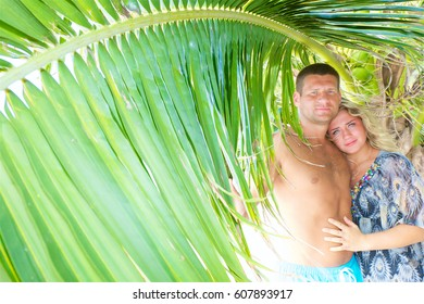 portrait of a happy couple in love with tropical coconut palm tree on the beach at summer time