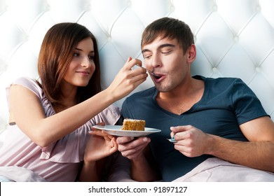 Portrait of happy couple lying in the bed. Girl feeding her boyfriend with spoon of tasty cake