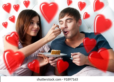 Portrait of happy couple lying in the bed. Girl feeding her boyfriend with spoon of tasty cake. Beautiful graphic red hearts are flying around