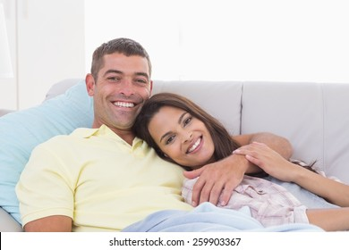 Portrait of happy couple lying on sofa at home